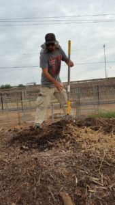 Tony works the compost pile at the community garden